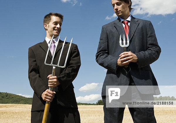 Zwei Männer halten Gartengeräte nebeneinander.