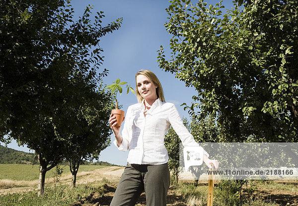 Frau  die sich auf eine Spatenhaltepflanze stützt.