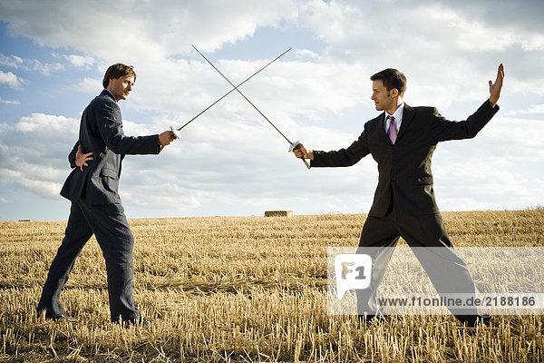 Geschäftsleute fechten im Weizenfeld.