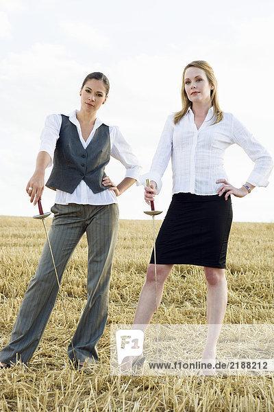 Zwei Frauen stehen mit Schwertern auf einem Weizenfeld.