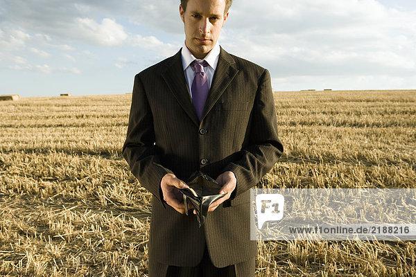 Mann mit leerer Brieftasche im Weizenfeld.