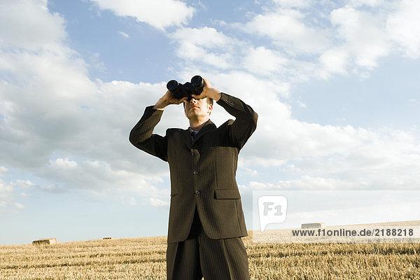 Ein Mann  der ein Fernglas im Weizenfeld benutzt.