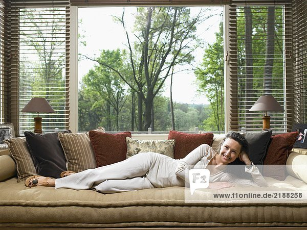 Woman lying on couch in living room smiling.