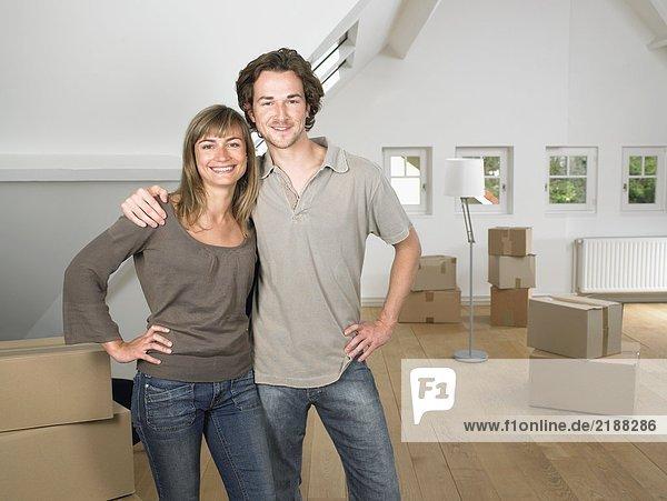 Ein Paar zieht lächelnd in ein neues Zuhause ein.