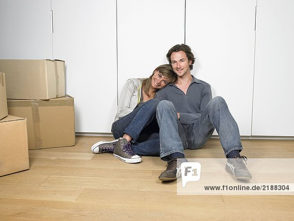 Couple sitting on floor smiling with moving boxes nearby.