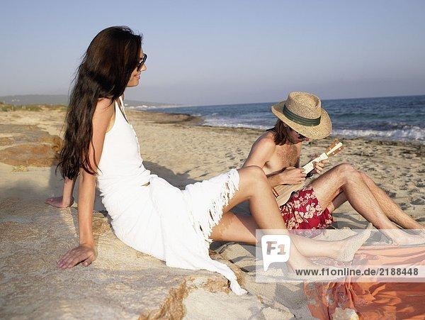 Mann spielt eine Ukulele am Strand  während eine lächelnde Frau zusieht.