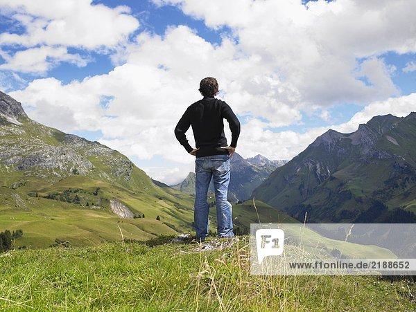 Ein Mann  der auf Berge schaut.