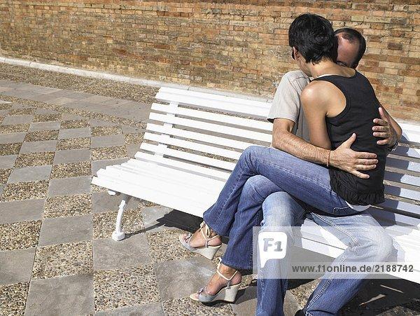 Ein paar Küsse auf einer Bank.