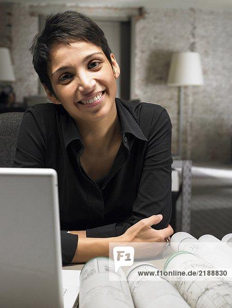 Architektin am Schreibtisch sitzend  lächelnd  Portrait