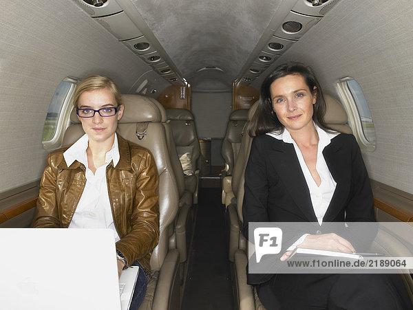 Zwei Frauen sitzen in einem Privatjet.