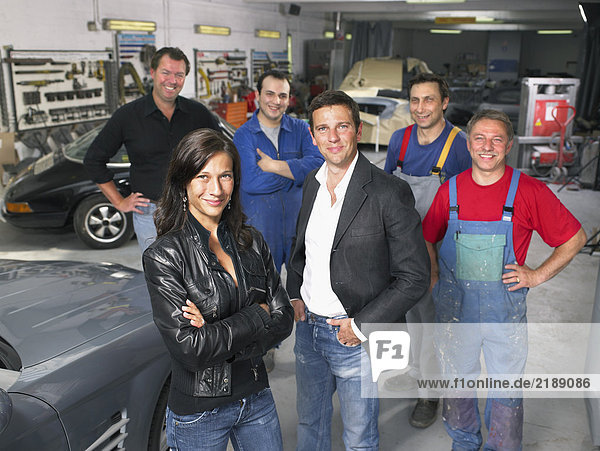 Group of workers and bosses in a garage.