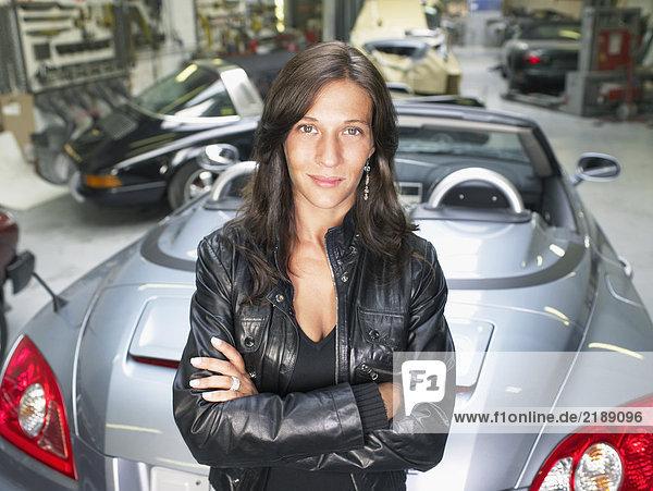 Porträt einer Frau  die sich auf ein graues Cabriolet in einer Garage stützt.