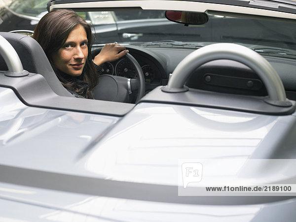 Frau in einem Cabriolet mit Blick auf die Kamera.