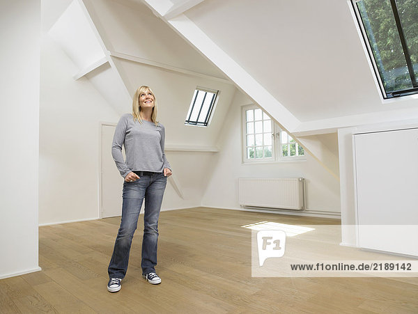 Woman standing and looking up inside empty white loft.
