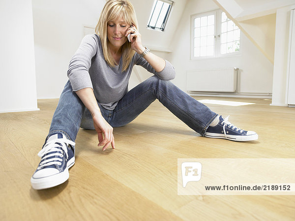 Relaxed woman seated on wooden floor giving a call with her cellular. White empty loft.