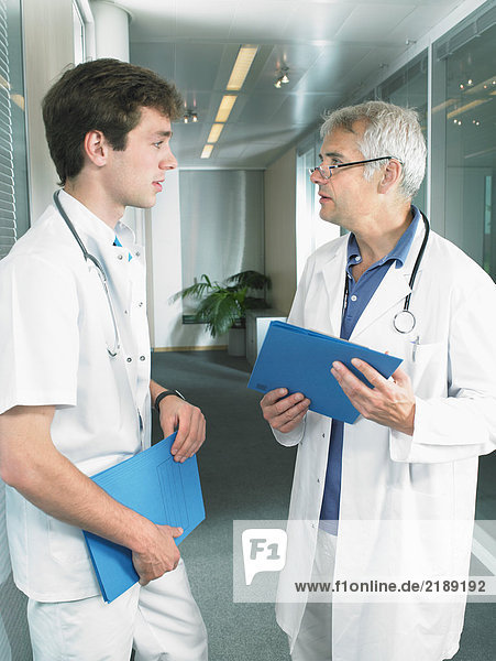 Mature doctor and young doctor in discussion in a lobby of a hospital.