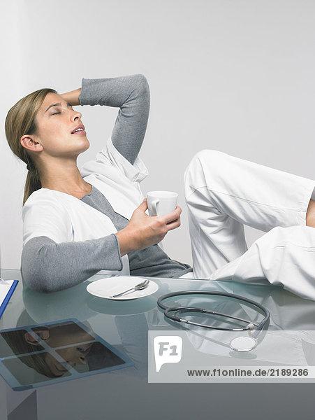 Eine Ärztin entspannt sich an ihrem Schreibtisch.