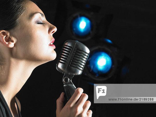 Sängerin mit Mikrofon elegantes schwarzes Kleid blaue Flecken.