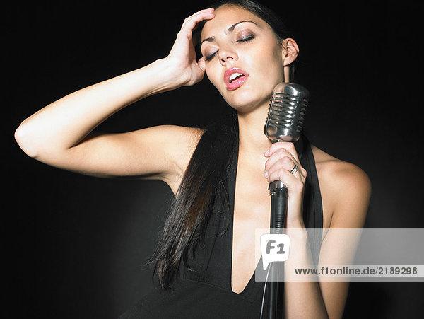Sängerin mit Mikrofon elegantes schwarzes Kleid Portrait.