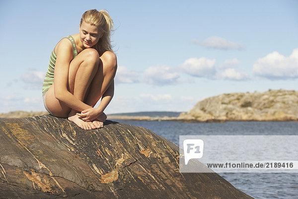 Junge Frau beim Yoga auf Steinen.