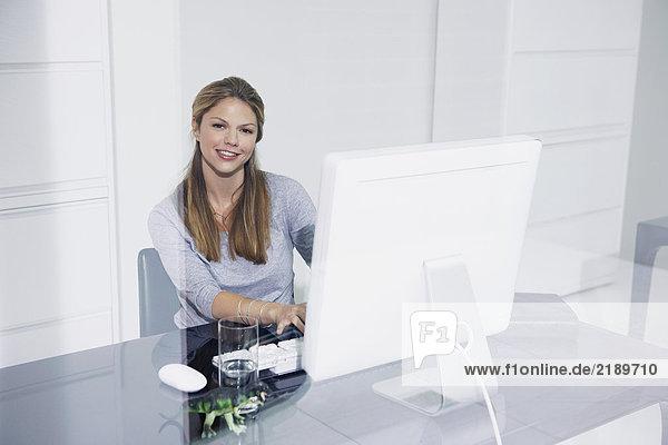 Frau im Büro am Schreibtisch lächelnd.