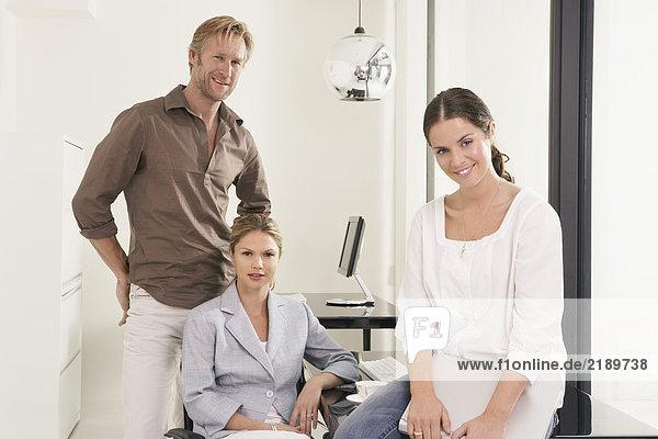 Mann und zwei Frauen im Büro sitzen auf dem Schreibtisch.