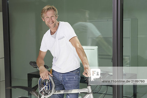 Young man in office building with bicycle.