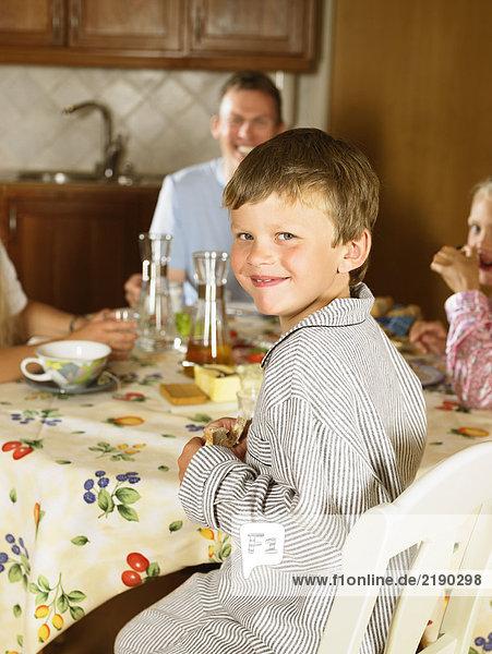Familie sitzt am Küchentisch und frühstückt lächelnd.
