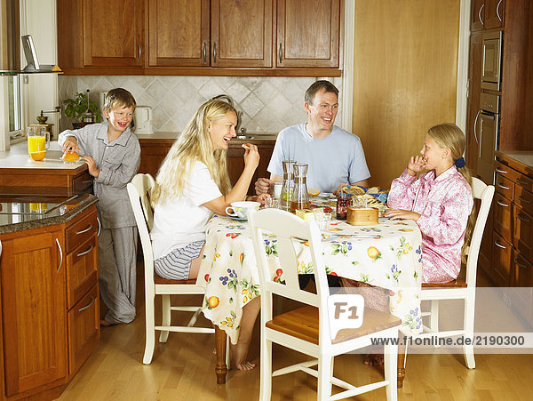 Family sitting at kitchen table eating breakfast smiling.