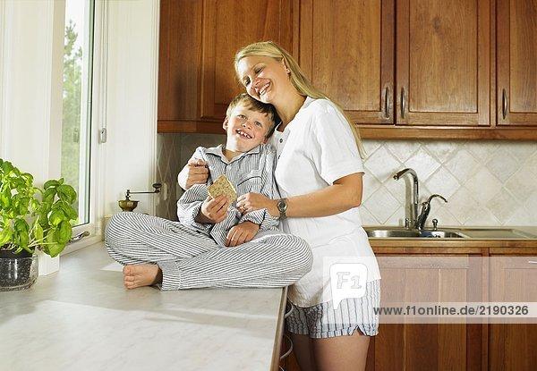 Frau und Junge halten ein Sandwich in der Küche.