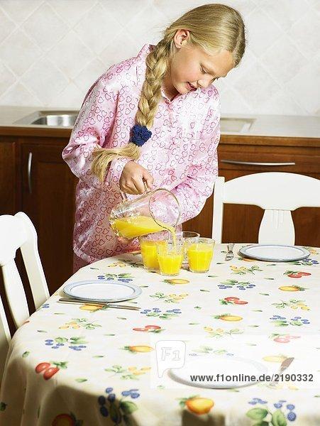 Ein junges Mädchen gießt Orangensaft in Gläser.