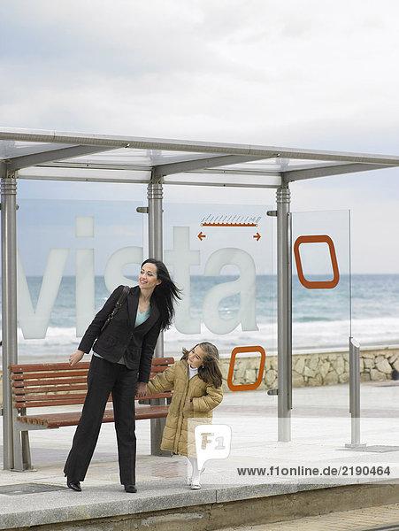 Mutter und Tochter (6-8) warten an der Strassenbahnhaltestelle an der Küste.