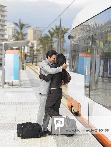 Geschäftsmann und Geschäftsfrau mit der Straßenbahn umarmend