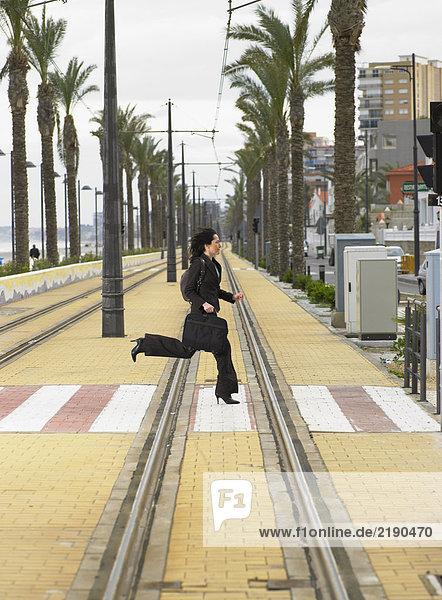 Geschäftsfrau  die mit der Straßenbahn über den Fußgängerüberweg rennt.