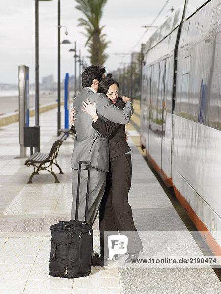 Paar in Anzügen an der Straßenbahnhaltestelle neben der Straßenbahn. Alicante  Spanien.