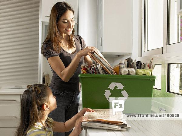 Mutter und Tochter (4-6) füllen Recycling-Box  lächelnd