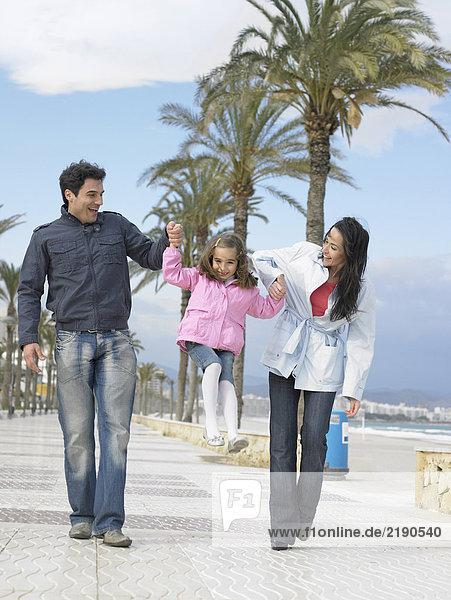 Mutter und Vater gehen auf einem palmengesäumten Bürgersteig am Meer entlang und schwingen die kleine Tochter (6-8). Alicante  Spanien.