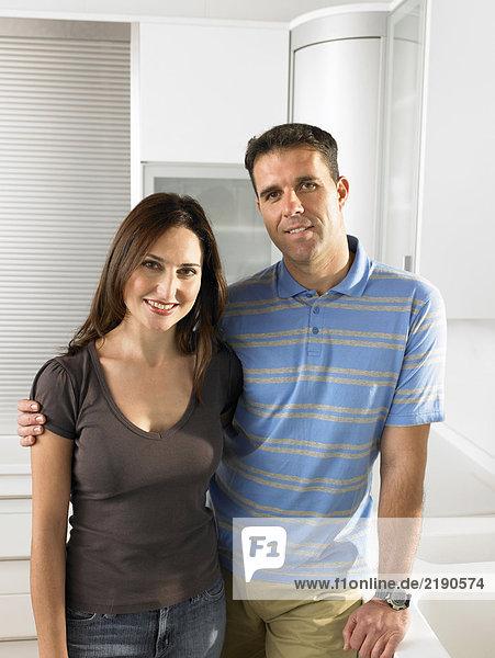 Paar steht in der Küche  lächelnd  Portrait