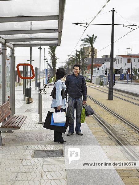 Junges Paar mit Einkaufsbummel an der Straßenbahnhaltestelle