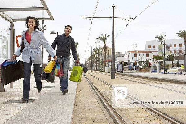 Junges Paar mit Einkaufsbummel zur Straßenbahnhaltestelle