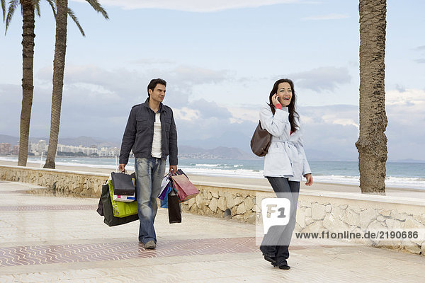 Frau mit Handy  Mann mit Einkaufen im Hintergrund