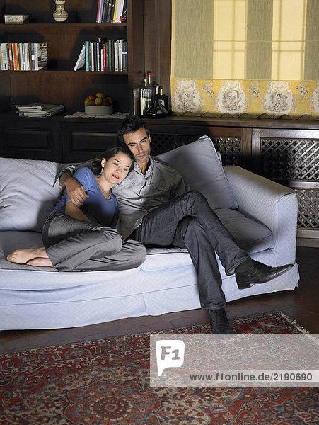 Junges Paar beim Fernsehen auf dem Sofa. Alicante  Spanien.