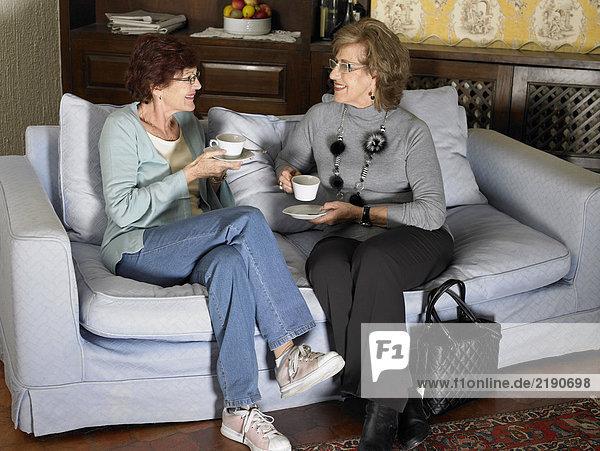 Zwei ältere Frauen sitzen auf dem Sofa und halten Tassen.