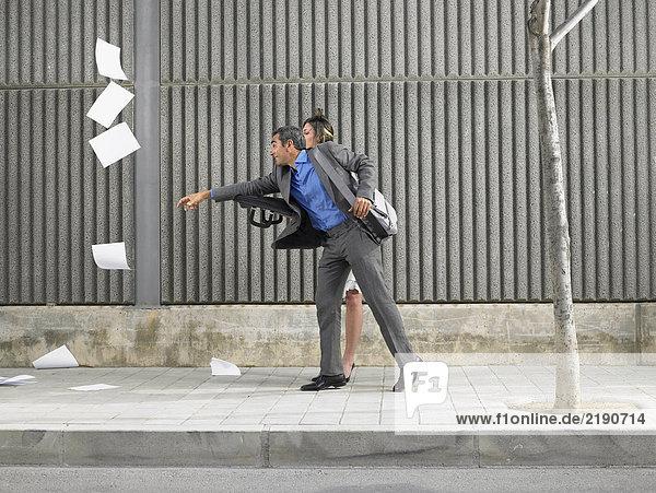 Älterer Mann und junge Frau jagen Papiere  die vom Wind über den Bürgersteig geblasen werden  Alicante  Spanien