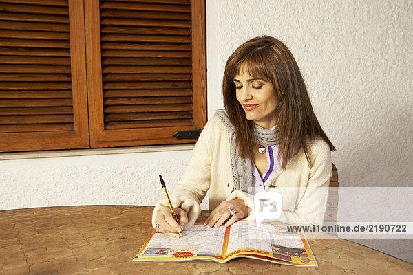 Frau am Tisch sitzend schreibt in Broschüre