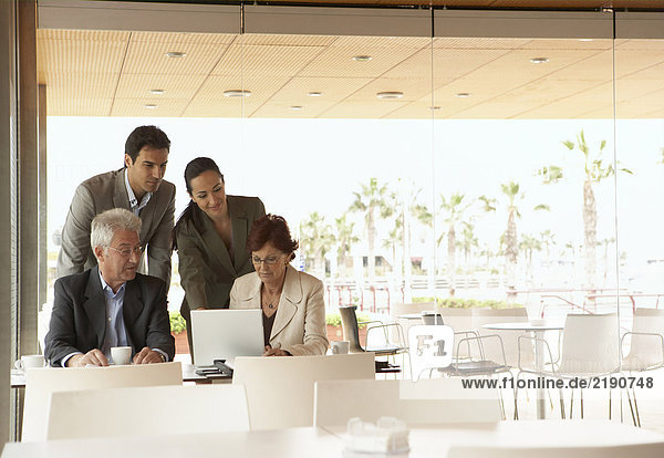 Zwei Männer und zwei Frauen bei einem Geschäftstreffen in einem Café mit Blick auf den Laptop. Alicante  Spanien.