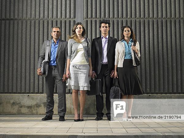 Ganzaufnahme von zwei Geschäftsfrauen und zwei Geschäftsleuten mit Blick auf die Betonwand  Alicante  Spanien