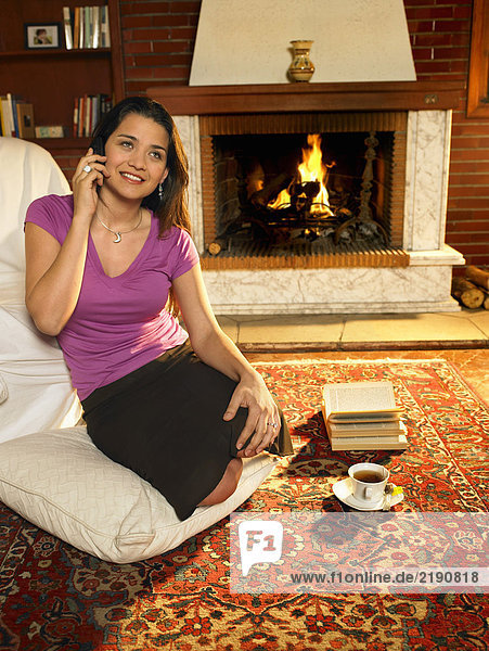 Young woman sitting on rug in front of fire using mobile phone  smiling
