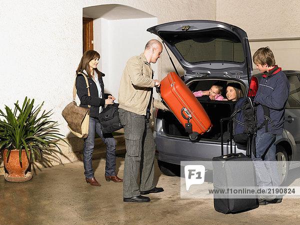 Familie beim Verladen des Gepäcks ins Auto auf der Einfahrt
