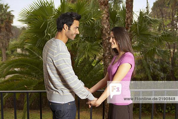 Junges Paar hält Hände auf dem Balkon stehend  lächelnd